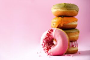 Stack of glazed colorful assorted donuts with sprinkles on pink background. Copy space. Sweet